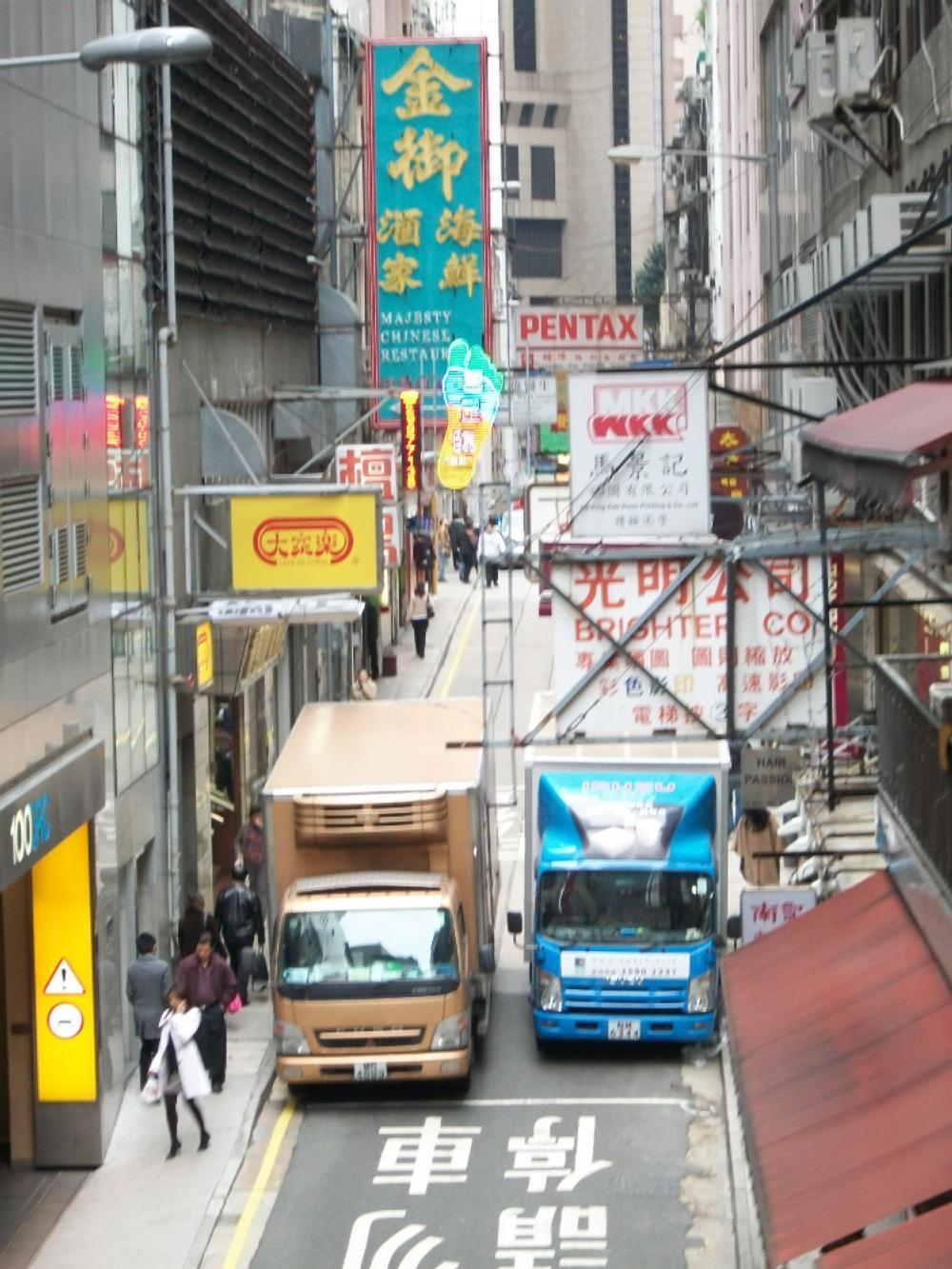 Two trucks in the middle of Hong Kong city street