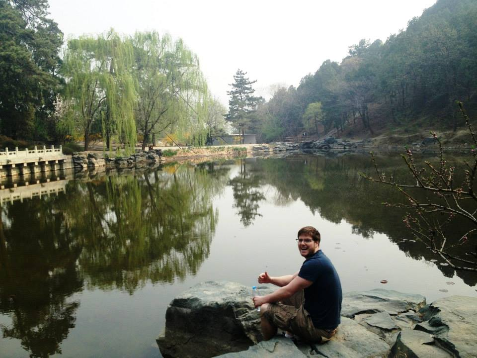 Student sitting near a Chinese reflecting pond